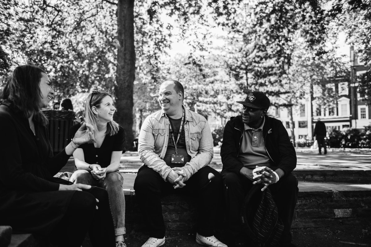 Four people talking and laughing outside